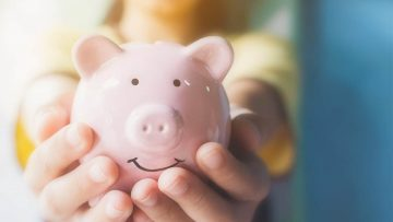 A child holding out a piggy bank