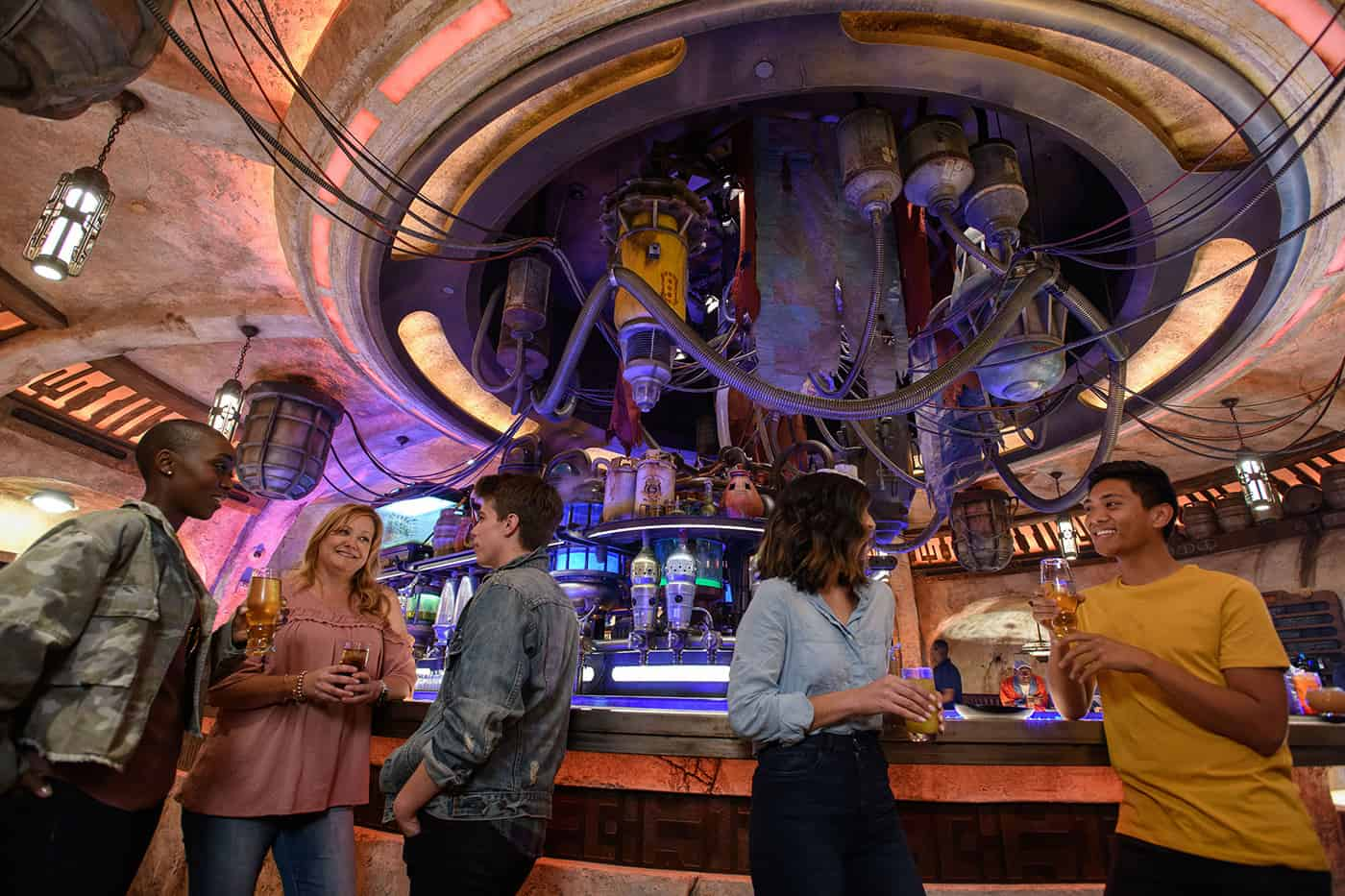 A few adults hanging out in Oga's Cantina in Star Wars Land