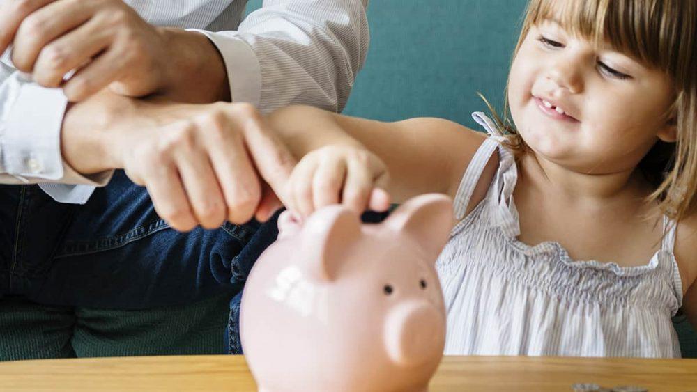 A child adds money to a piggy bank