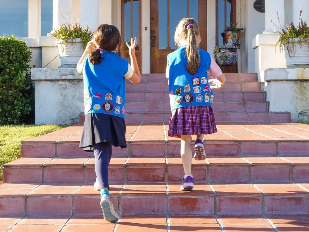 Walking up some steps to sell Girl Scout cookies